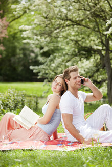 Couple with cell phone and book on picnic blanket in park - CvK000148