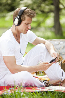 Man on picnic blanket listening to music in park - CvK000224