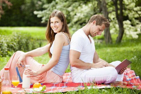 Happy couple with digital tablet having a picnic in park - CvK000203