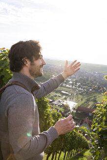 Germany, Bavaria, Volkach, winegrower in vineyard enjoying view - FKF000776