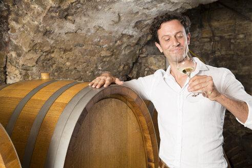 Man in wine cellar tasting wine - FKF000822