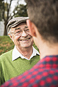 Senior man smiling at adult grandson - UUF002637