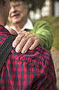 Senior man smiling at adult grandson - UUF002638