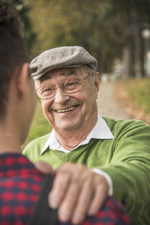 Senior man smiling at adult grandson - UUF002639
