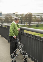 Senior man with wheeled walker on bridge - UUF002650
