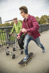 Happy senior man with wheeled walker and adult grandson with skateboard - UUF002653