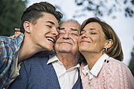 Smiling senior man with daughter and grandson in park - UUF002674