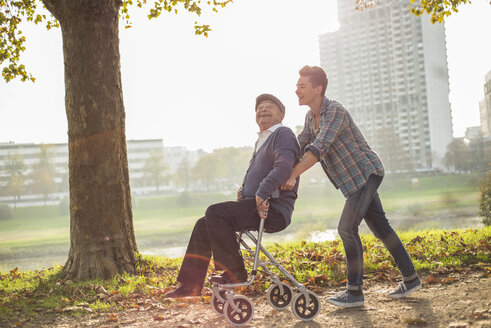 Grandson pushing happy senior man with wheeled walker - UUF002690