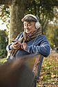 Senior man on park bench with cell phone and headphones - UUF002717