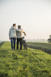 Senior man and grandson in rural landscape with bicycle - UUF002700