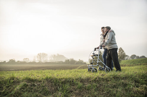 Senior man and grandson in rural landscape with wheeled walker - UUF002706