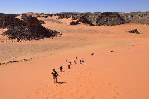Africa, Algeria, Sahara, Tassili N'Ajjer National Park, Tadrart region, Group of people on sand dune at Oued Bouhadian - ES001470