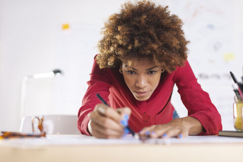 Portrait of young female architect working at her desk - EBSF000335