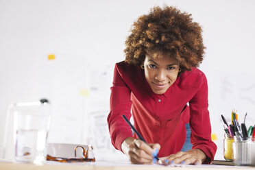 Portrait of smiling young female architect working at her desk - EBSF000337