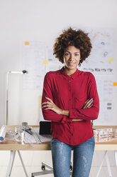 Portrait of smiling young female architect with crossed arms standing at her office - EBSF000344