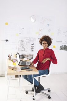 Young female architect with laptop at her desk - EBSF000350