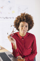 Portrait of smiling young female architect with glasses in her hand - EBSF000353