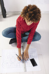 Young female architect working on the floor of her office - EBSF000360