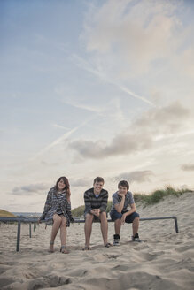 Netherlands, three smiling teenagers sitting in a row on the beach - MVC000145