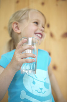 Happy blonde girl holding glass of water - FSF000347