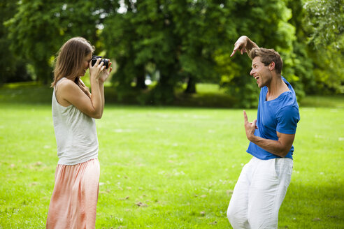 Happy couple in park taking photos - CvKF000158