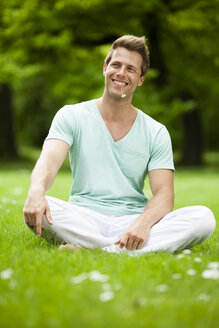 Happy man sitting on meadow in park - CvKF000165