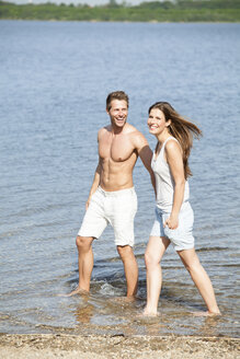 Happy couple wading in water - CvKF000175