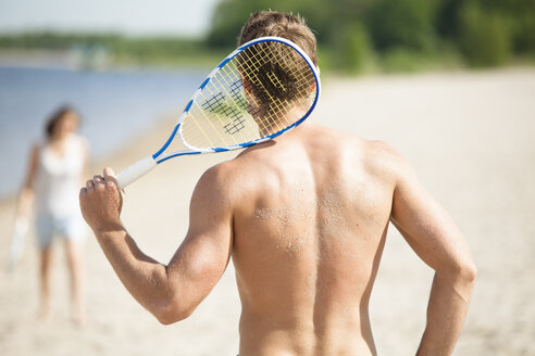 Man with badminton racket on the beach - CvKF000186