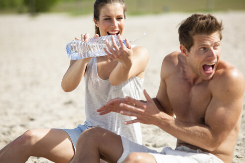 Playful couple splashing with bottle of water on the beach - CvKF000191