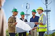 Business partners looking at wind turbine schematics with engineer - ZEF002248