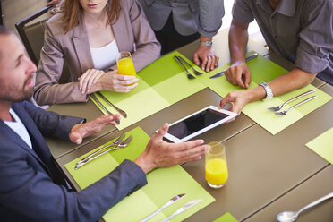 Businessman showing digital tablet to colleagues at dining table - ZEF002217