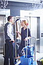 Hotel bell boy and cleaning lady socializing in lobby - ZEF002435