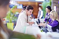 Businessman registering at hotel reception - ZEF002430