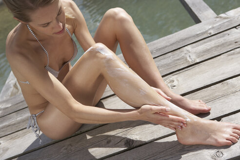 Woman sitting on planks putting on suncream - FSF000370