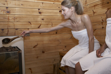 Two young women sitting in a sauna - FSF000372