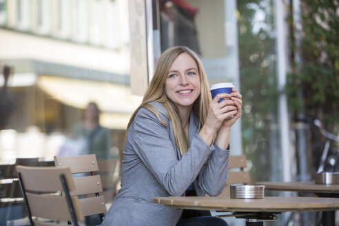 Smiling young women sitting at pavement cafe with coffee to go - SHKF000025