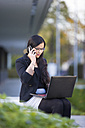 Young businesswoman with laptop telephoning with smartphone - MAD000098