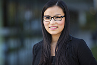 Portrait of smiling young businesswoman wearing glasses - MAD000105