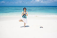 Maldives, Ari Atoll, young woman doing yoga exercise on the beach - FLF000573