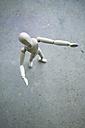 Wooden manikin standing on grey ground - MYF000718