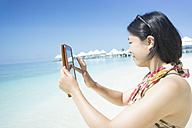Maldives, Ari Atoll, young woman taking photograph with her mini tablet - FLF000580
