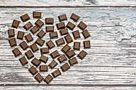 Heart formed by pieces of chocolate on wood - SARF001047