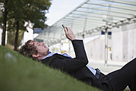 Businessman lying on a meadow using his smartphone - RBF002061