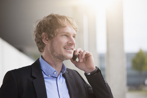 Portrait of smiling businessman telephoning with smartphone - RBF002070