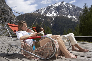 Switzerland, two young women sitting on deck chairs on sun deck - FSF000379
