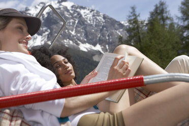 Switzerland, two young women relaxing on deck chairs on a sun deck - FSF000381