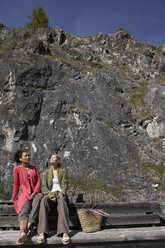 Switzerland, two young women sitting on backrest of a bench sunbathing - FSF000363