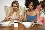 Two female friends eating cake and drinking tea in a cafe - FSF000353