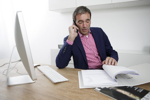 Businessman in office on the phone - GDF000608