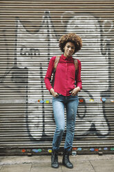 Smiling young woman standing in front of roller shutter with graffiti - EBSF000371